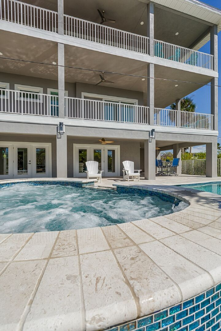 The backyard hot tub and exterior patios of this vacation house for rent in Fort Myers FL.