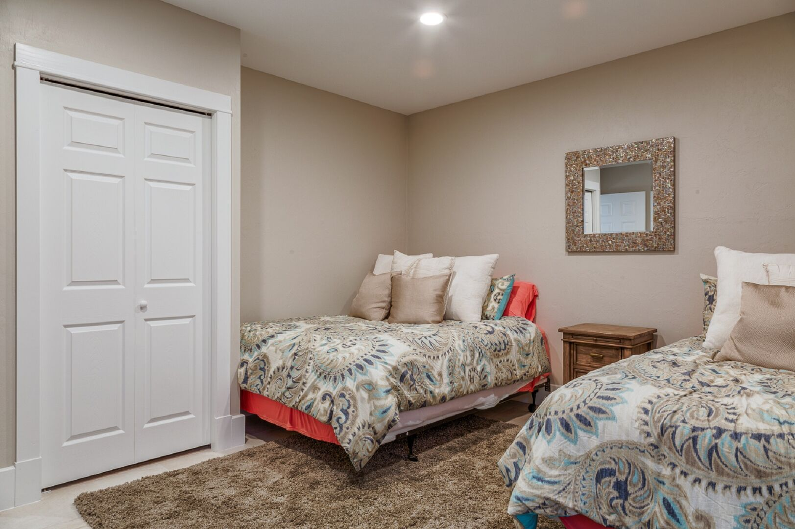 Two large beds side by side, with a nightstand and mirror between them.