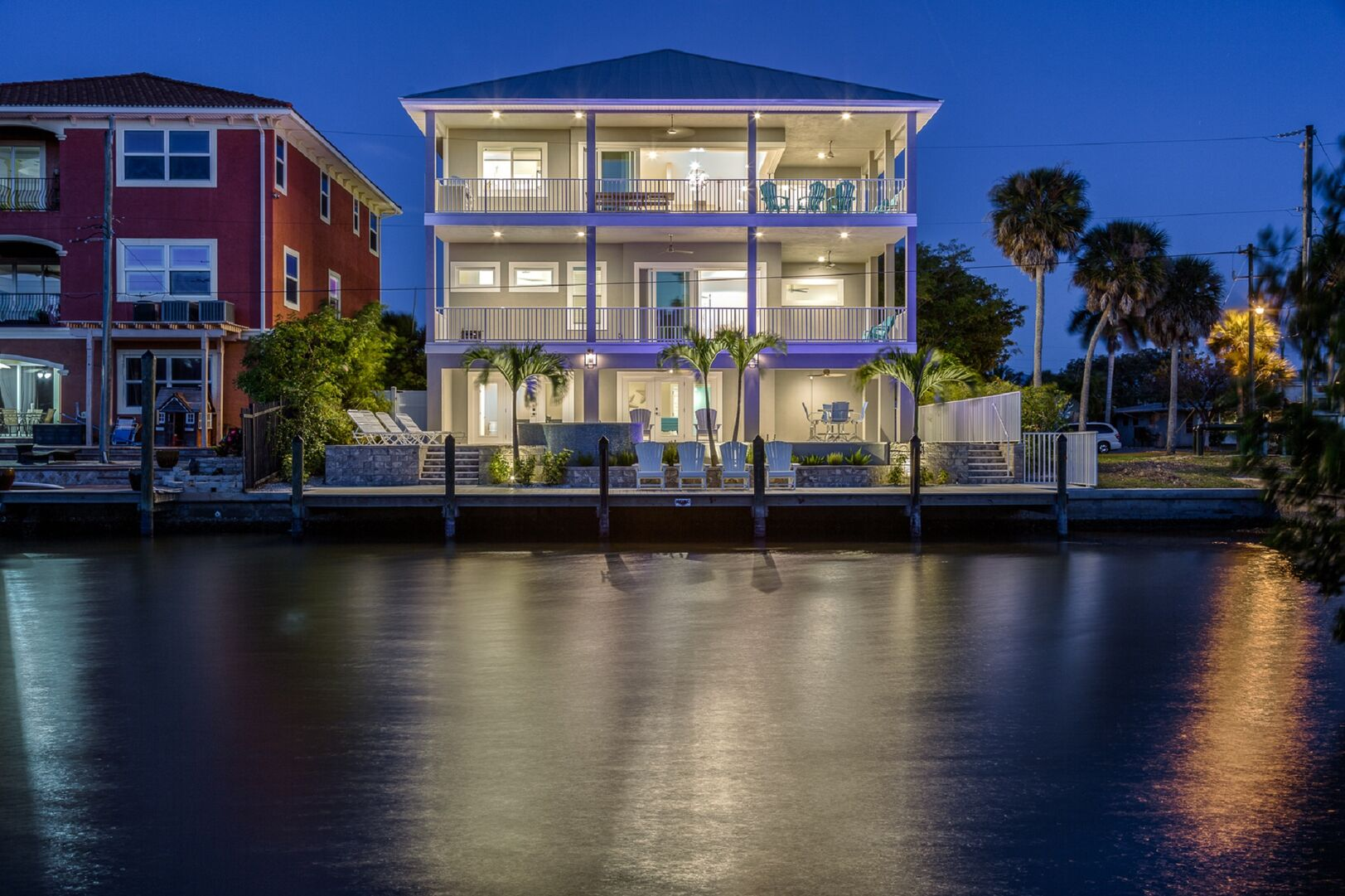 This vacation house for rent in Fort Myers FL as seen from across the bay, lit-up at night.