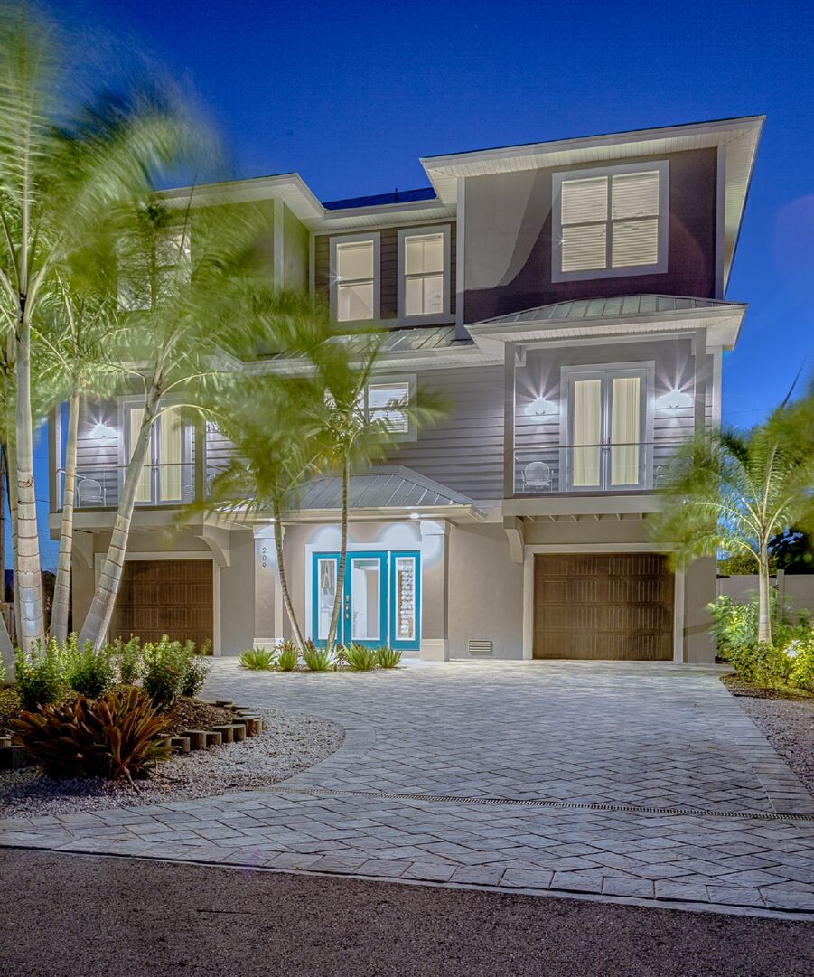 Front exterior of this vacation house for rent in Fort Myers FL, highlighted by palm trees.
