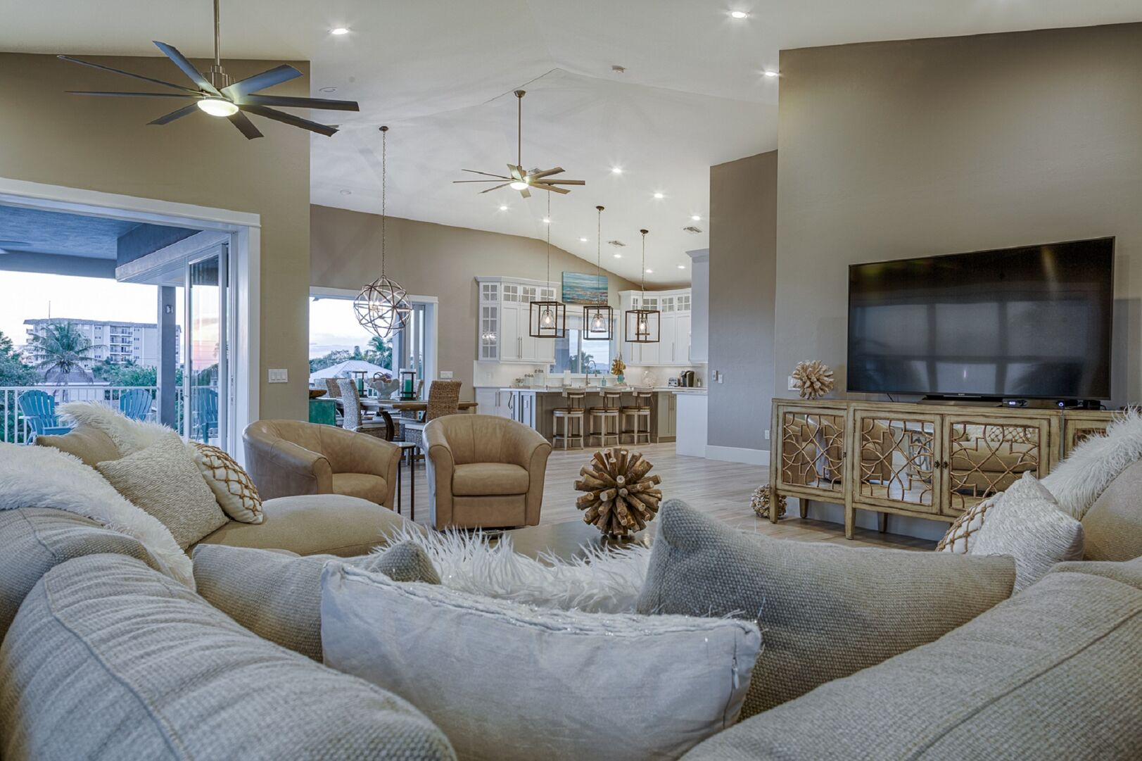 The living area of this vacation house for rent in Fort Myers FL, with a large sectional couch, TV on an entertainment center in front of it, and a view of the kitchen in the background.