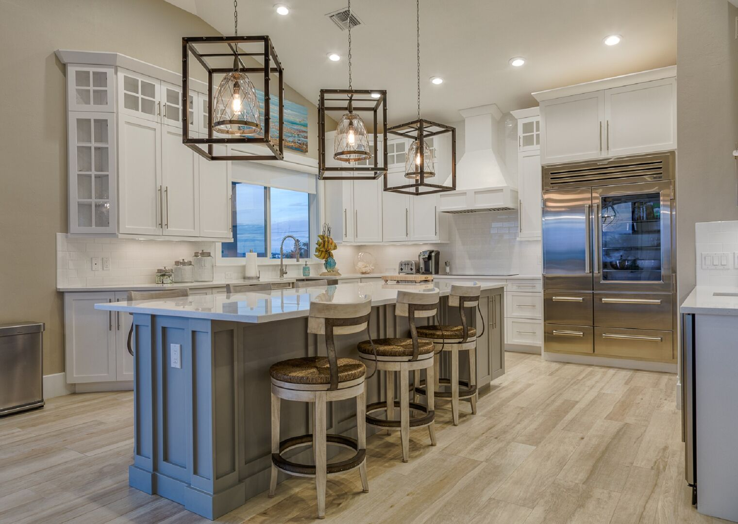 The kitchen island, with ornate hanging lights above it, and ample seating alongside.