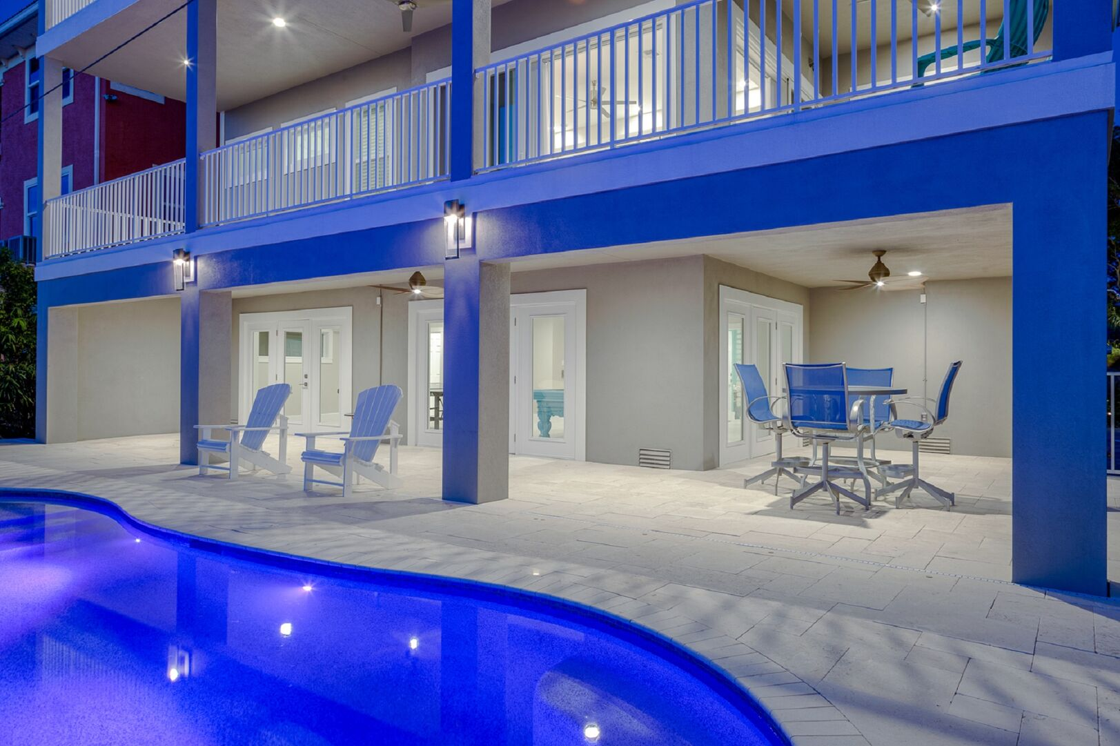 The bottom floor patio of this vacation house for rent in Fort Myers FL, right by the lit-up pool.