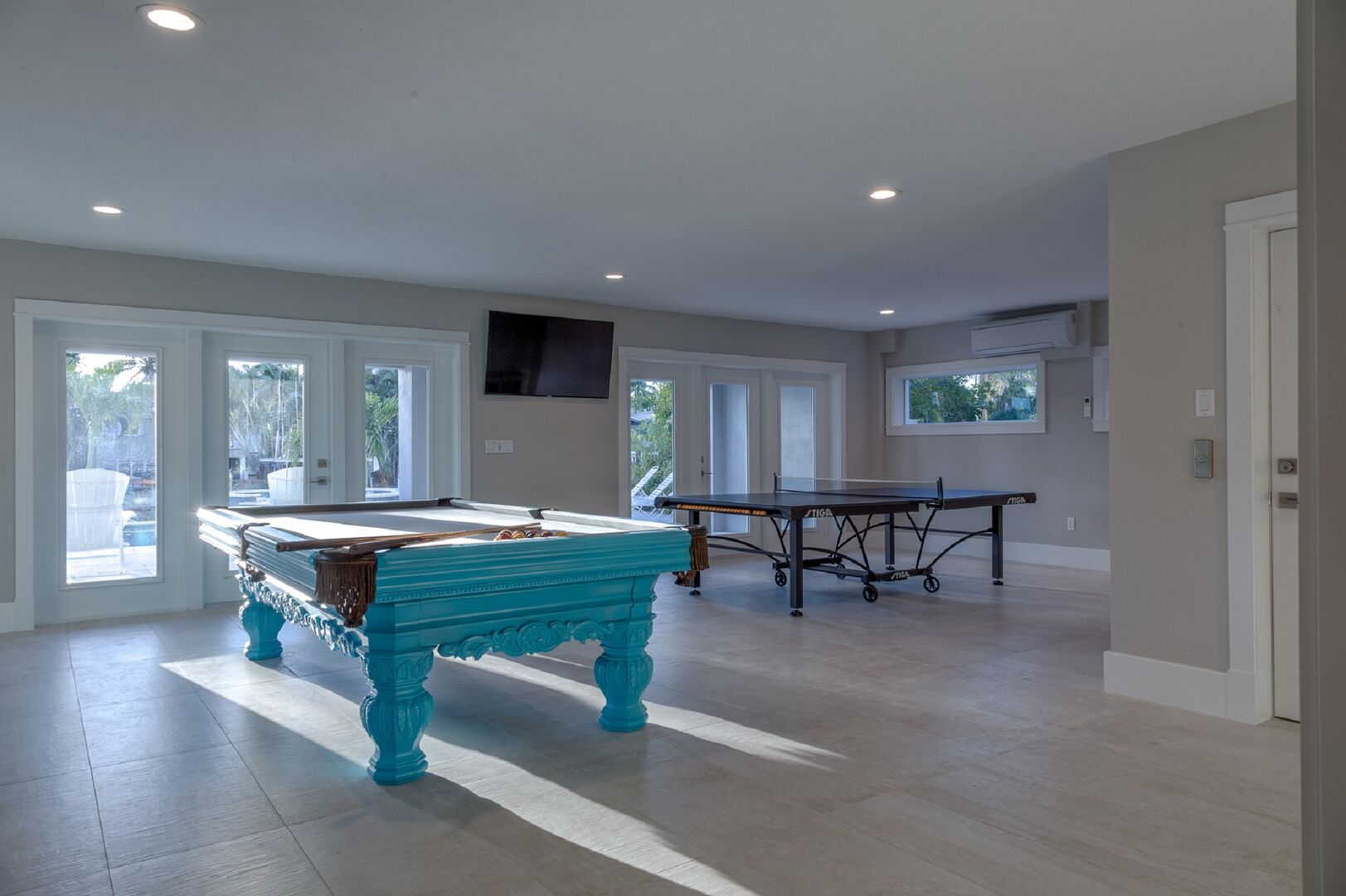 The game room of this vacation house for rent in Fort Myers FL, with wall-mounted TV, pool table, and table tennis.