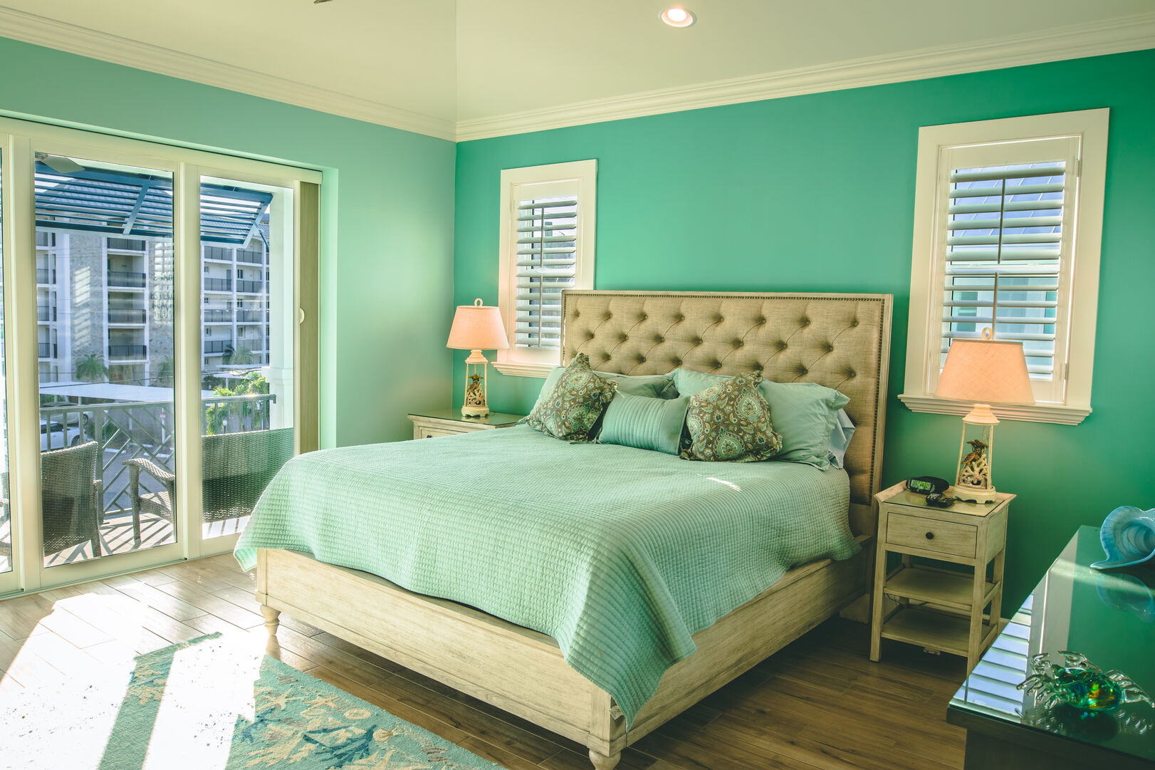 Green bedroom with large bed (also green), and twin nightstands, in front of a sliding glass door.