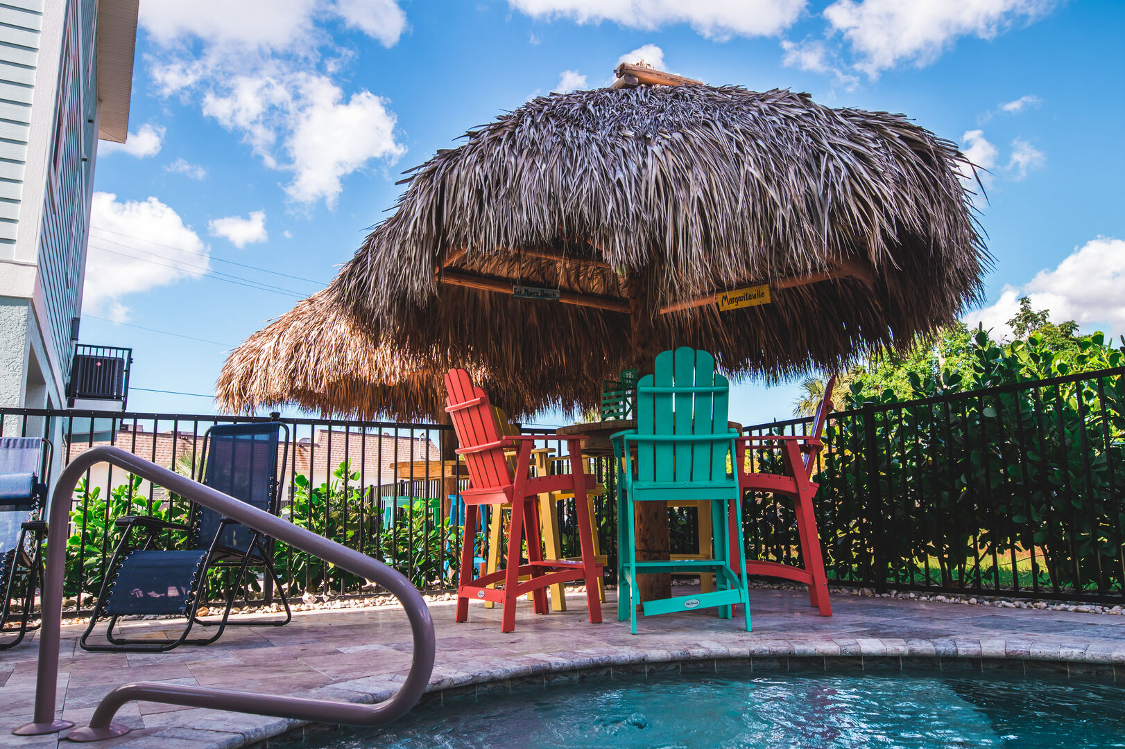 Seating and straw umbrella by the pool.