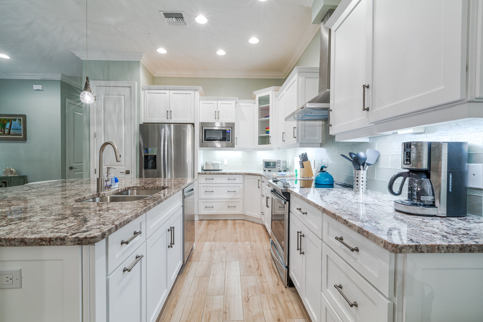 Kitchen complete with center island with sink, granite countertops, and modern appliances.
