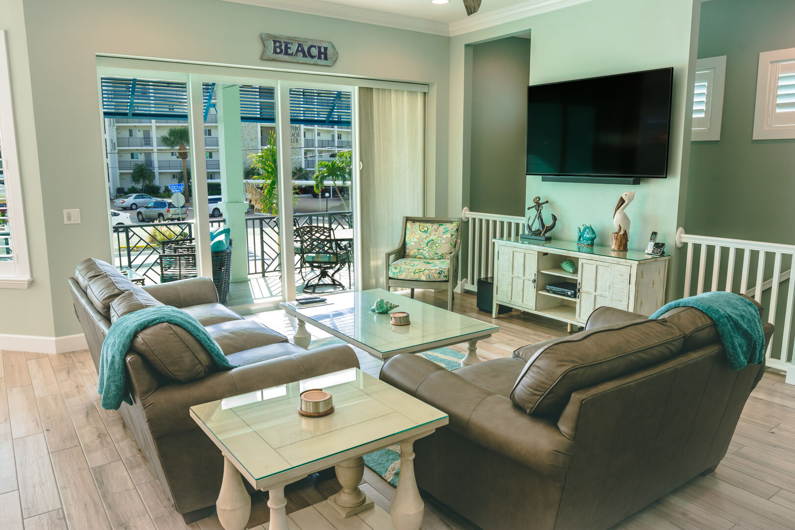The living area of this Fort Myers Beach Rental, with two couches, a coffee table, and wall mounted tv.