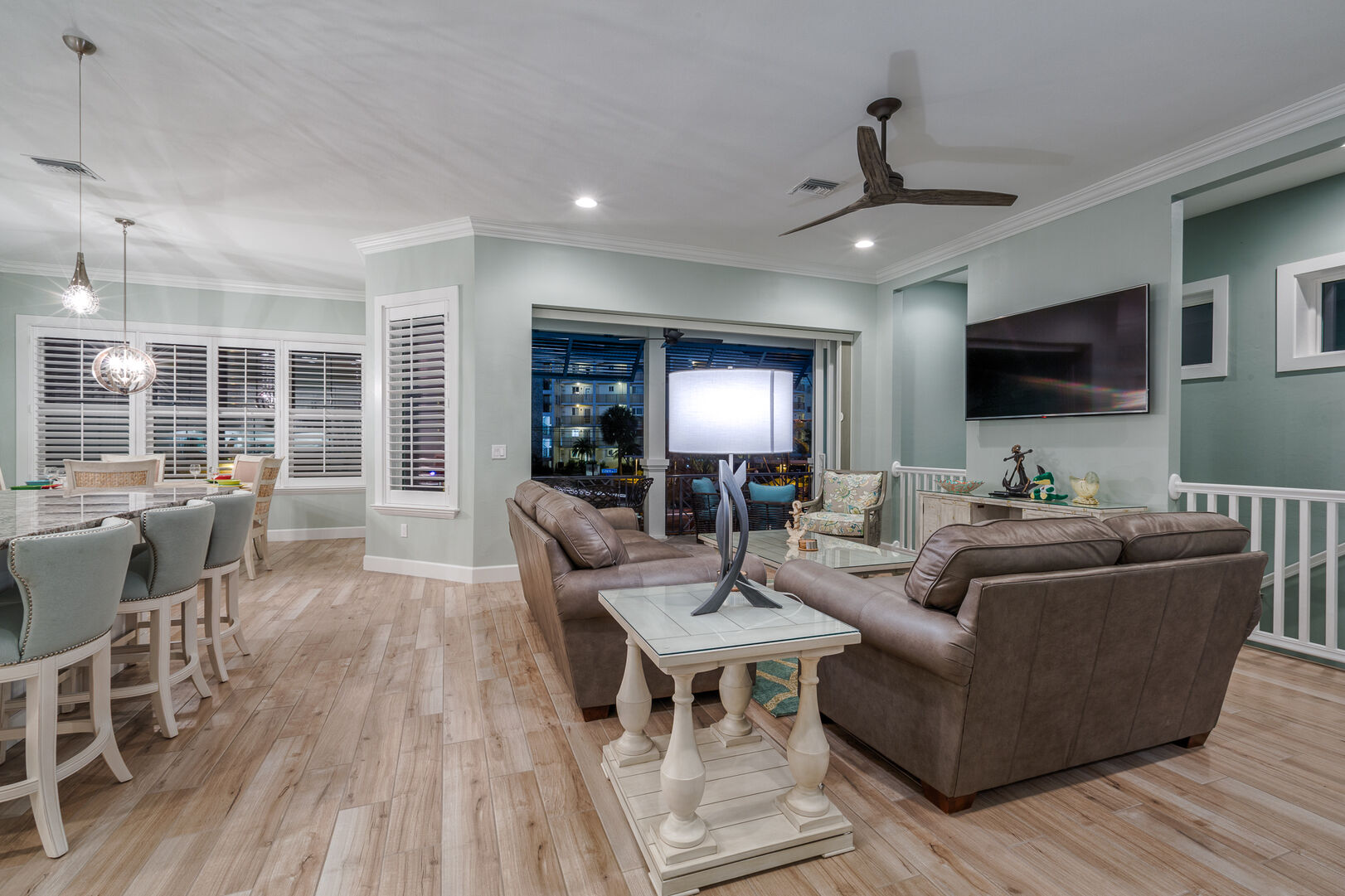 Living area with ample seating and wall-mounted TV, all in front of a large glass door.