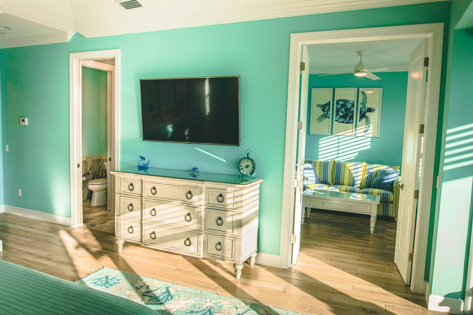 Wall-mounted TV sits above a dresser between doors to a bathroom and a small living area.