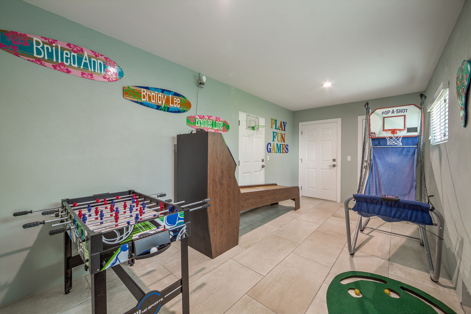 Another view of the game room that shows the foosball table, skeeball table, and basketball hoop.