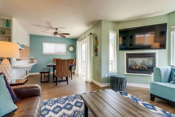 Bright and beachy living room with fireplace, flat screen TV and comfortable furniture.