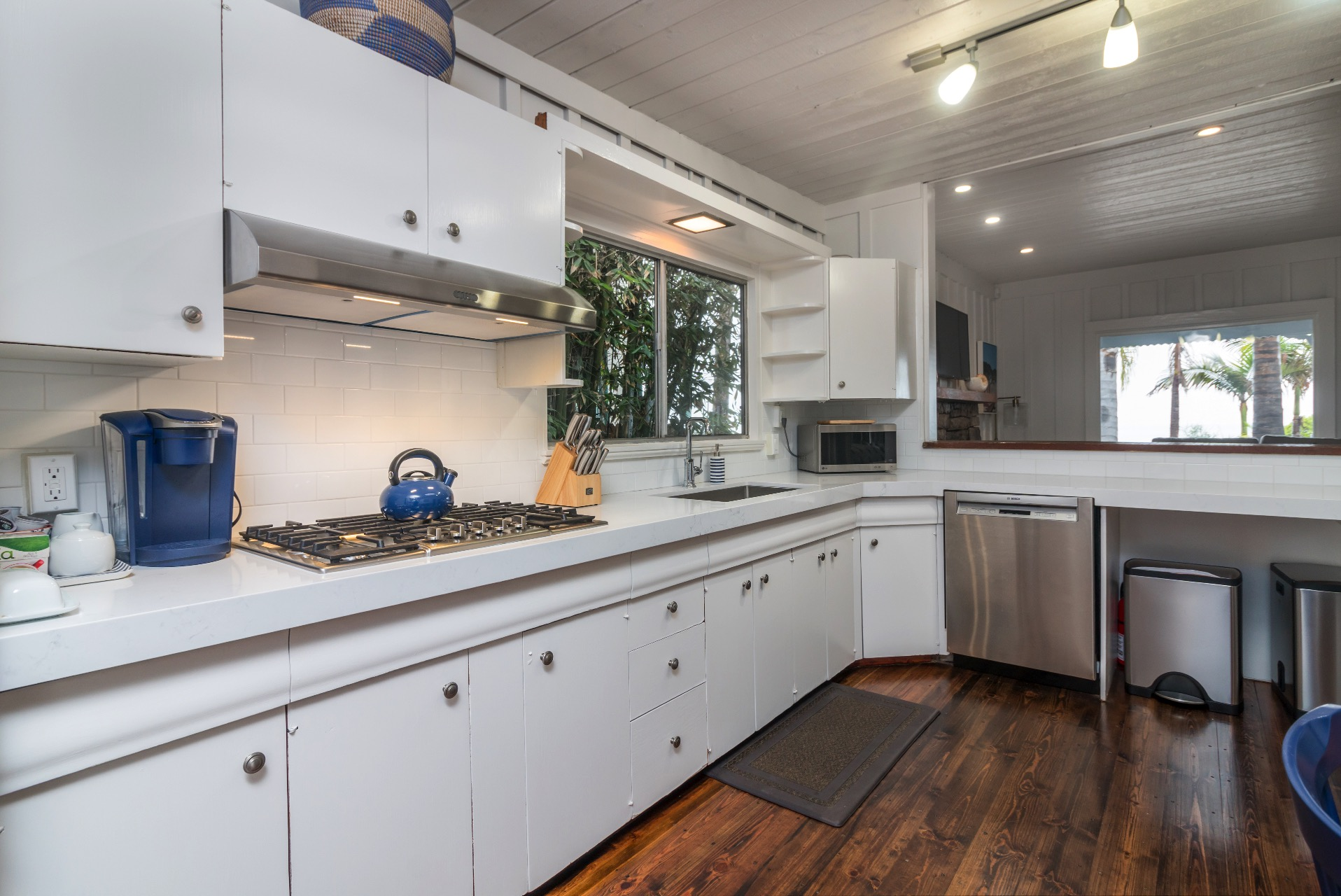 Kitchen has solid stone counter top, tile backsplash, new gas stove, dishwasher and stainless steel sink.