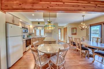 Breakfast Table and Dining Table with Chairs on the Kitchen, Refrigerator, and Ceiling Lamps.