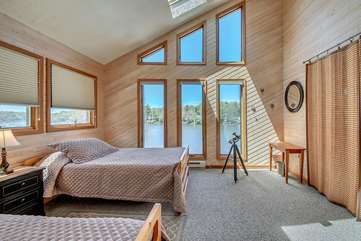 Bedroom with Two Beds, Nightstand, Mirror, Table, and Windows with Great Views.