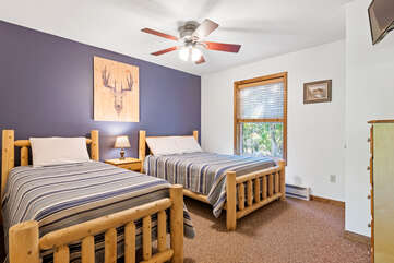 blue bedroom with two beds and a ceiling fan