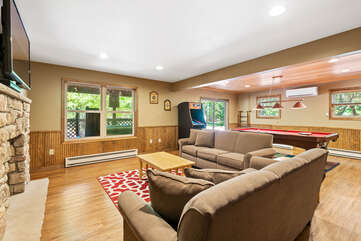 basement with two sofas and an arcade cabinet