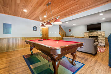 basement with pool table and couch