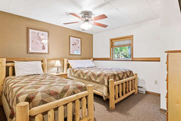 tan bedroom with two beds and ceiling fan