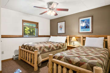 tan bedroom with two beds and pictures on the wall