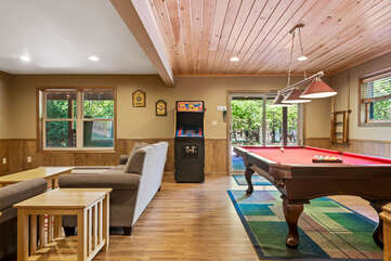 basement with couches, arcade machine and pool table