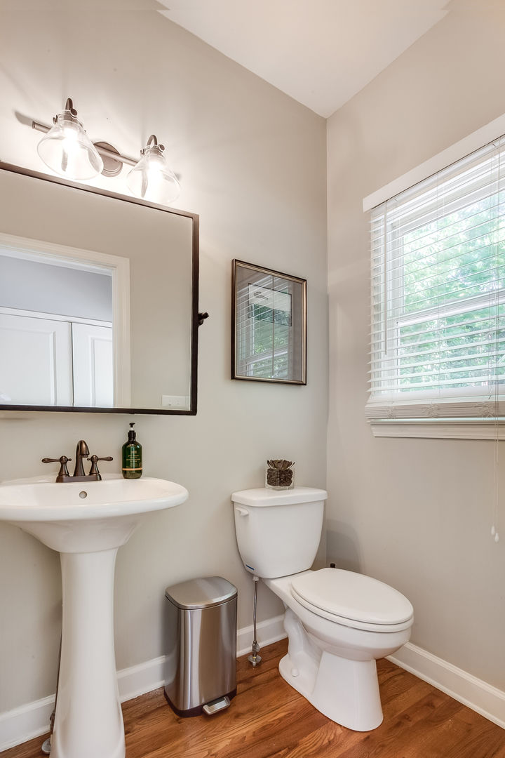 Bathroom with Pedestal Sink, Toilet, and Mirror.