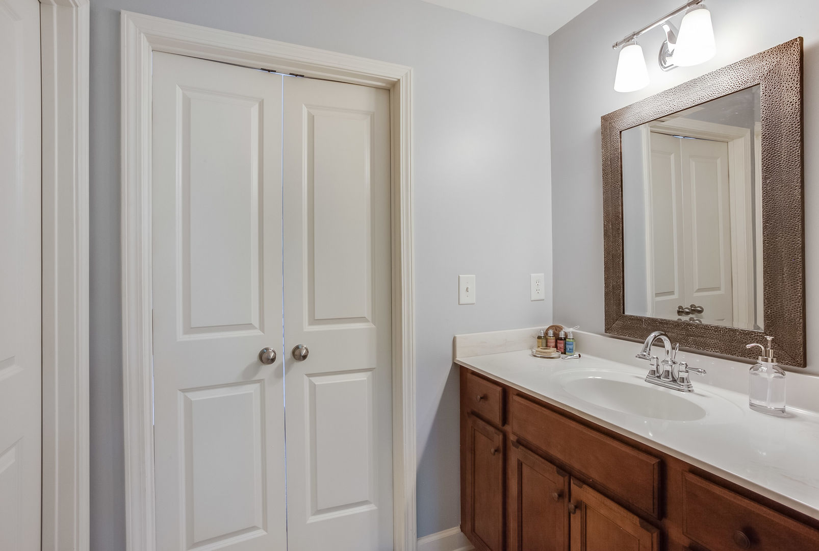 Single Vanity Sink, Mirror, Lamp, and Door.