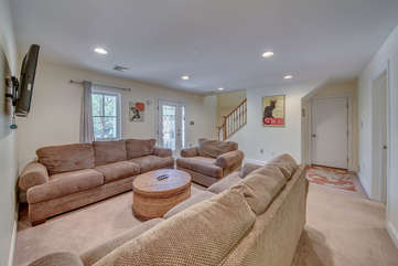 Lower floor living area with TV, three couches, and coffee table. Stairway in the background.