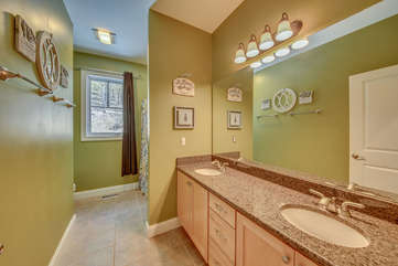 Bathroom with wide mirror, two sinks, and towel rack.