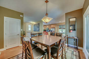 Dining room with table, chairs, and a view of the kitchen.