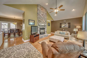 The great room of this Big Boulder rental, with three couches, TV, fireplace, and coffee table. Kitchen table visible in upper left.