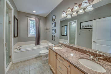 Double sink, wide mirror, toilet, and bathtub in the master bedroom of this Big Boulder rental.
