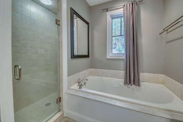 Bathtub next to the glass door of the walk in shower.