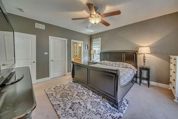 Master bedroom with bed, TV, nightstands, and the bathroom door open.