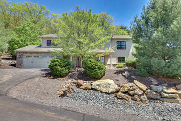 A picture featuring the front yard landscaping of this Big Boulder rental, with two large trees and rock landscaping. Driveway visible.