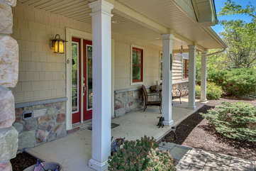 The front porch of this Big Boulder rental, with a few porch chairs and red double doors.