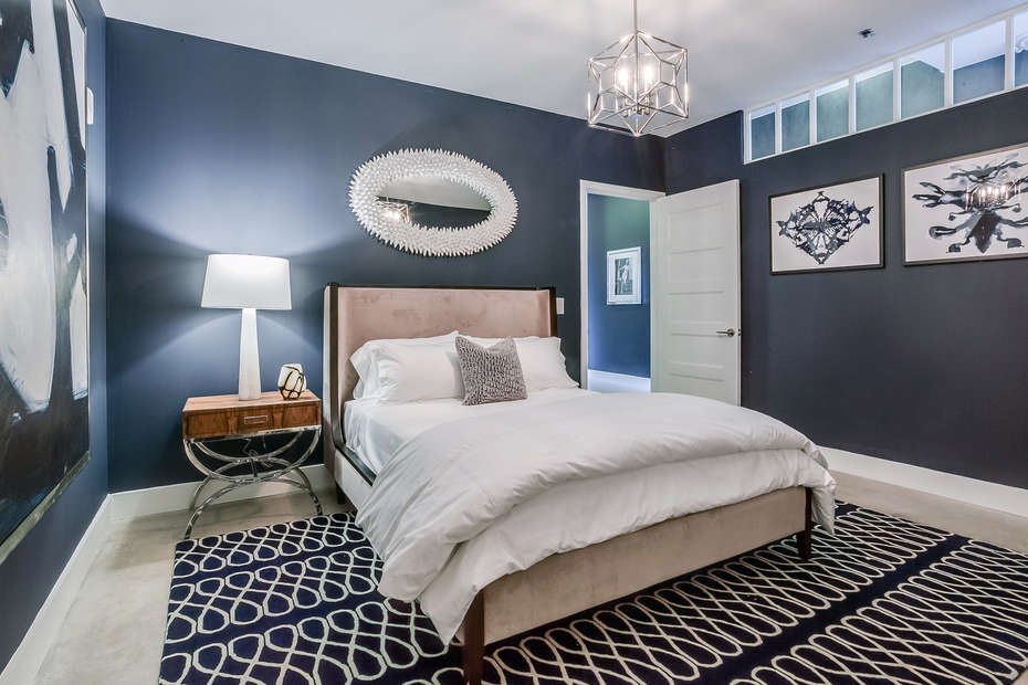Bedroom with Large Bed, Nightstand, Table Lamp, and Mirror.