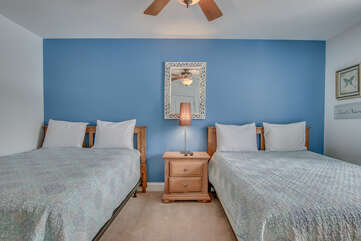 A nightstand with lamp, mirror and two beds, in one of this Big Boulder rentals many bedrooms.