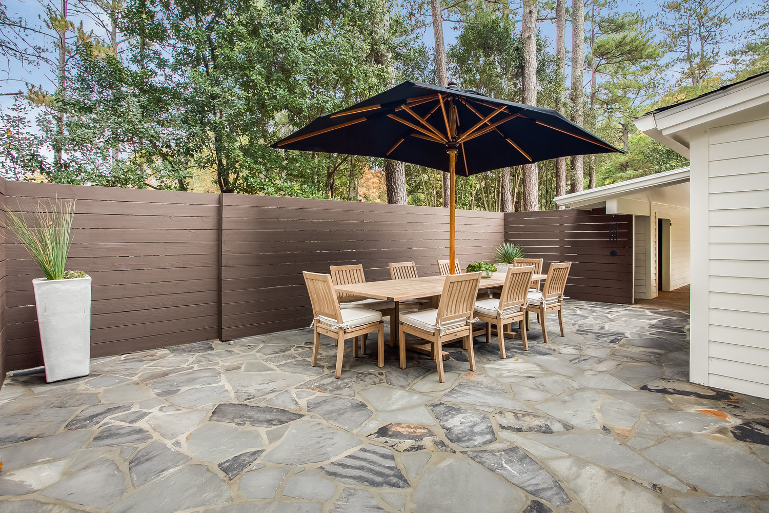 Outdoor Dining Table with Umbrella, Chairs, and in the Backyard.