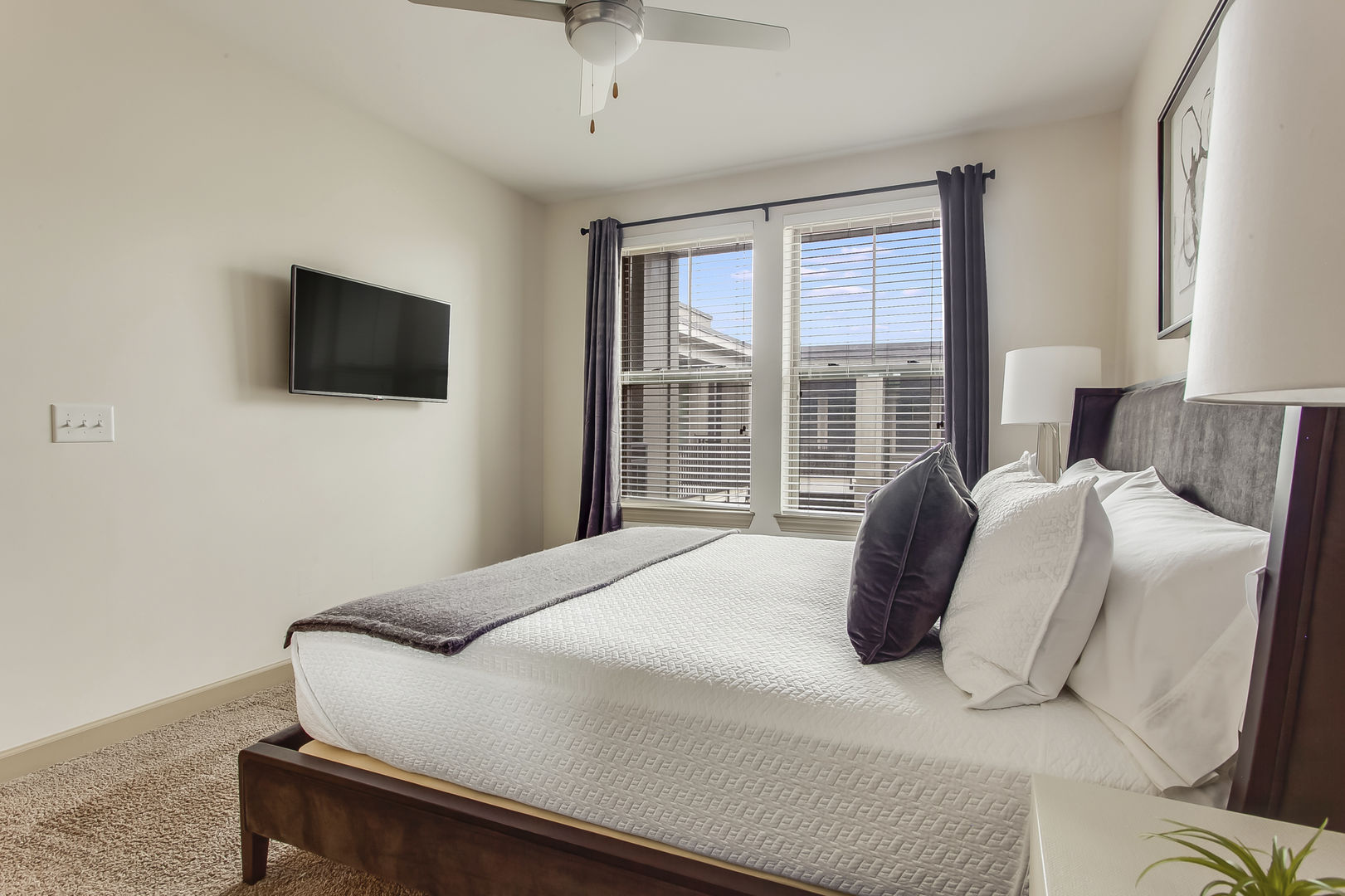 The bedroom at this Atlanta Rental Apartment has a wall mounted TV and a ceiling fan