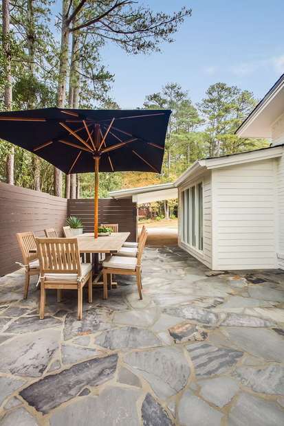 Backyard with Outdoor Dining Table with Umbrella and Chairs.