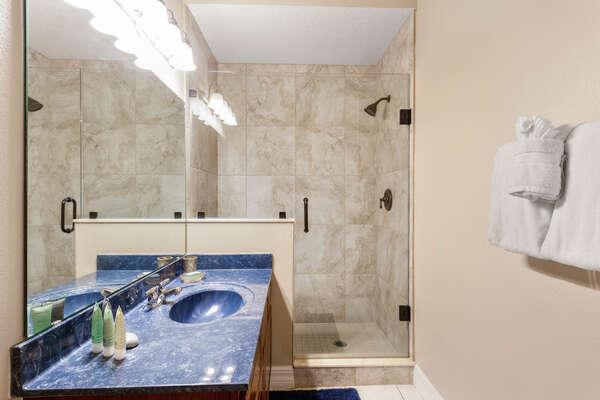 This bedroom has a walk in shower, toilet & vanity unit