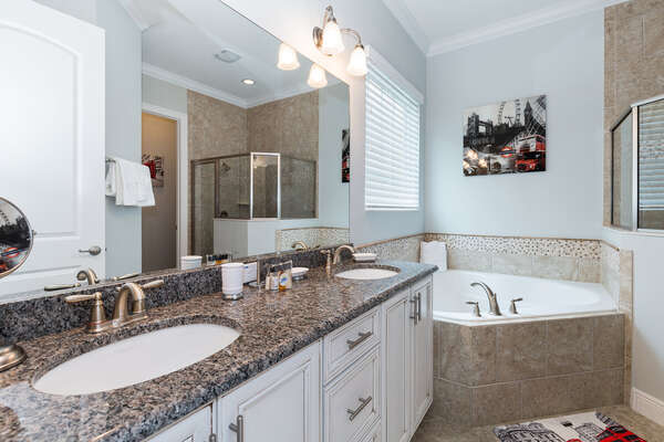 Master bathroom on the ground floor with dual vanity, garden tub, and walk-in shower
