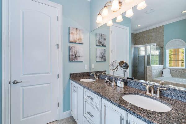 En-suite bathroom with walk in shower, garden tub, and dual vanity