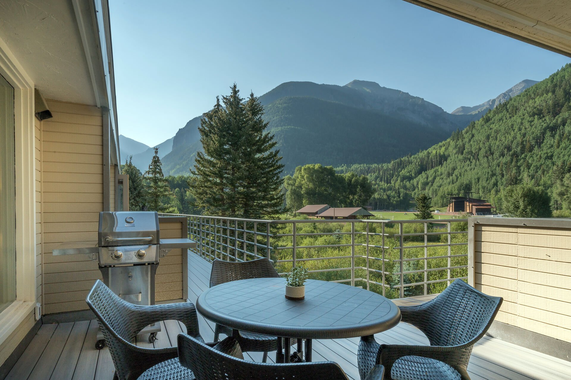 Deck outside of this Telluride Mountain rental with grill and seating.