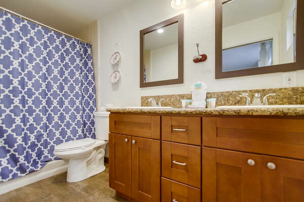 Dual Sink Vanity, Toilet, and Shower.