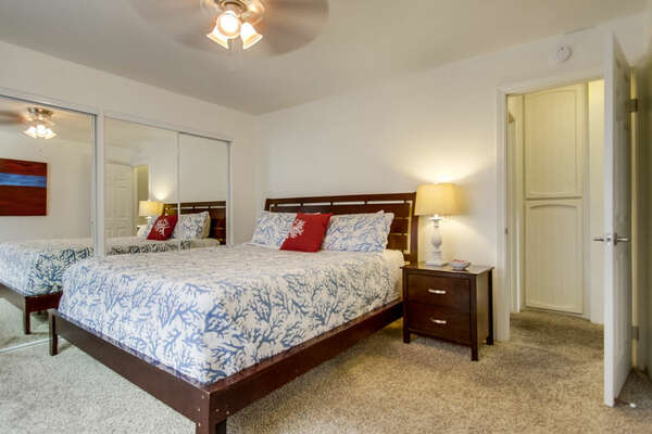 Bedroom with Large Bed, Nightstand, Ceiling Fan, and Mirror Closet Doors.