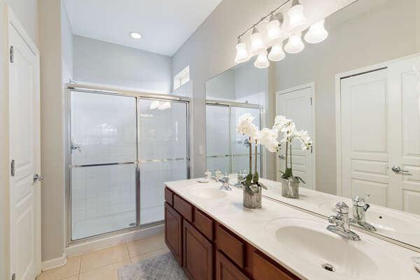 En-suite bathroom with dual vanities and glass walk-in shower
