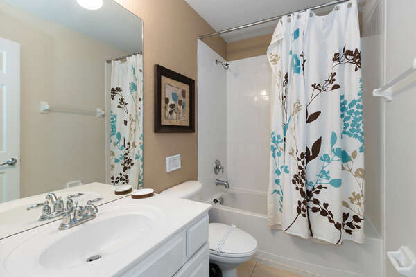 The en-suite bathroom has a combination shower and tub