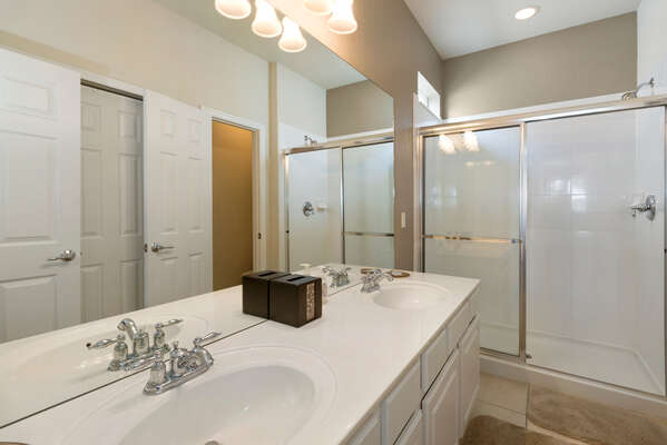 The en-suite bathroom has dual sinks and a walk-in glass shower